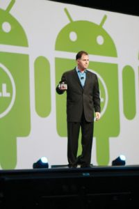 Michael Dell giving a speech wearing a black suit standing on a stage in front of green Dell robot icons.